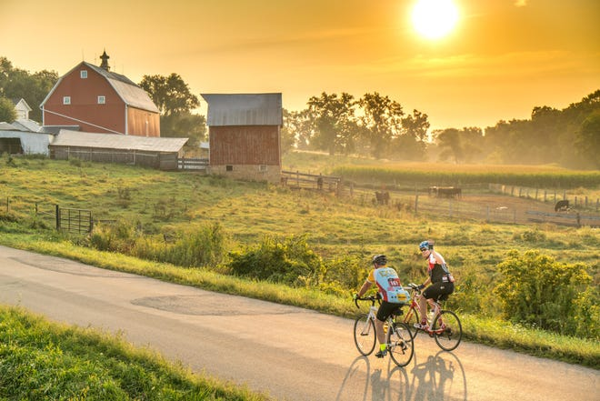 One of the Ride Across Wisconsin founders waves to the camera as he rides with a friend through Wisconsin's beautiful agricultural communities.