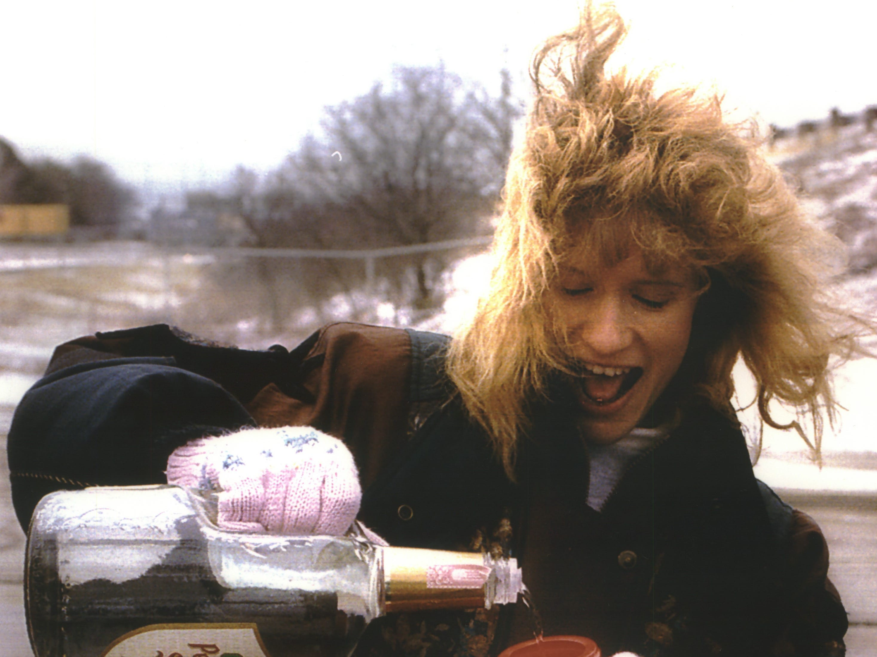 Julie Pesch adds peppermint schnapps to hot chocolate to stave off the unseasonable chill at County Stadium as she and her co-workers from Deluxe Data tailgate before opening day on April 5, 1994. This photo was published on the front page of the April 5, 1994, Milwaukee Journal. In the home opener, the Milwaukee Brewers defeated the Oakland A's, 11-7.