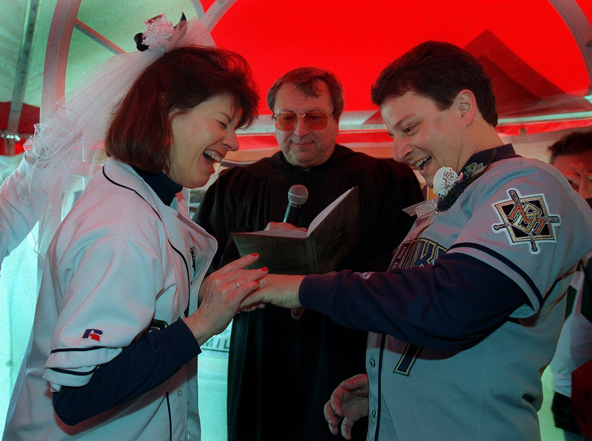 Brewers fans Claire Stann and Dean Wonser are joined holy matrimony by Judge Michael Hurt before the Milwaukee Brewers' home opener on April 16, 1999, at County Stadium. The ceremony took place in the new east parking lot, part of the preparations for Miller Park. In the game, which was supposed to be the Brewers' final opening day at County Stadium, Milwaukee lost to the Chicago Cubs, 9-4. (A deadly crane collapse later that summer delayed completion of Miller Park until the 2001 season.)