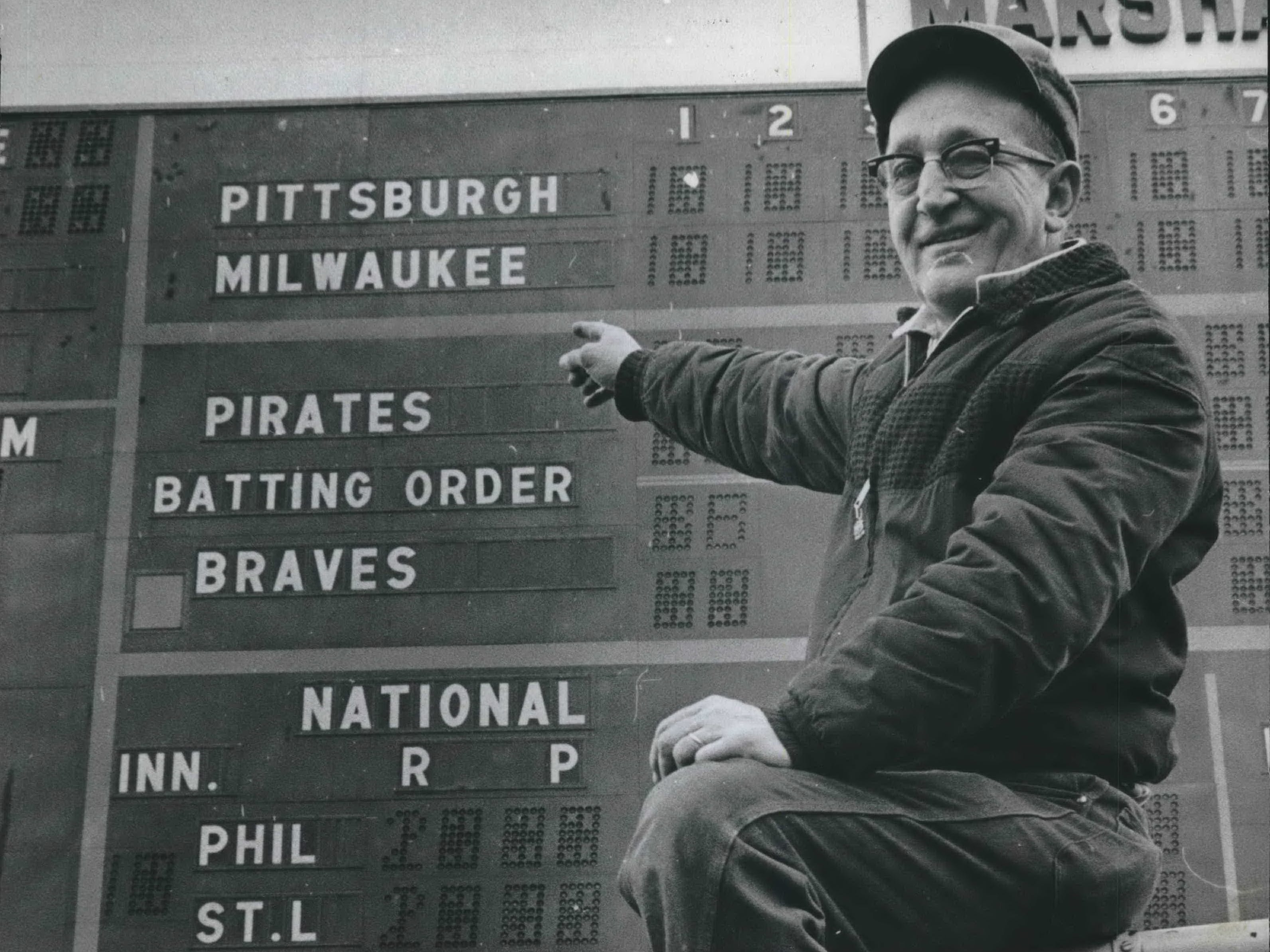 Everything is in readiness at County Stadium for opening day of the 1966 baseball season - provided, that is, a court can force the Braves to return to Milwaukee. Pointing to the scoreboard, which shows Pittsburgh at Milwaukee, is Edward Tuchalaski, a County Park Commission employee. (Spoiler alert: It didn't happen; the Braves stayed in Atlanta, and Milwaukee got the Brewers in 1970.) This photo was published in the April 3, 1966, Milwaukee Sentinel.
