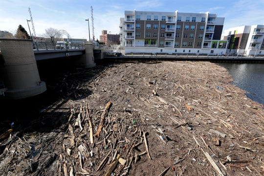 Trees, branches and debris create a logjam Tuesday at the Pleasant Street Bridge on the Milwaukee River.