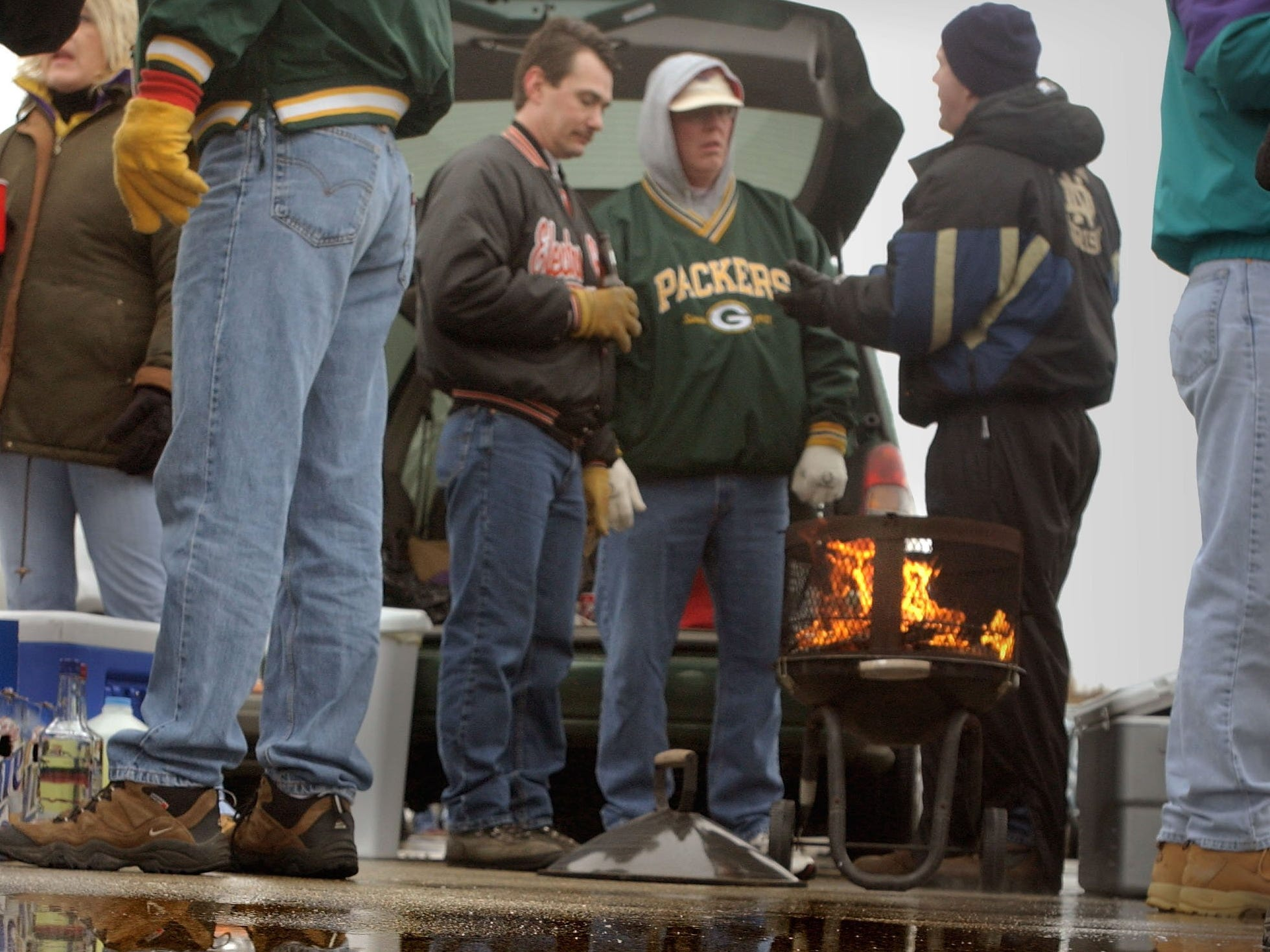 Fans Scott Ciske (from left), Bob Koster and Dave Kuhr keep the home-opener fires burning, despite the soggy and chilly conditions, outside Miller Park on April 4, 2003. The Milwaukee Brewers lost the home opener to the San Francisco Giants, 4-3.