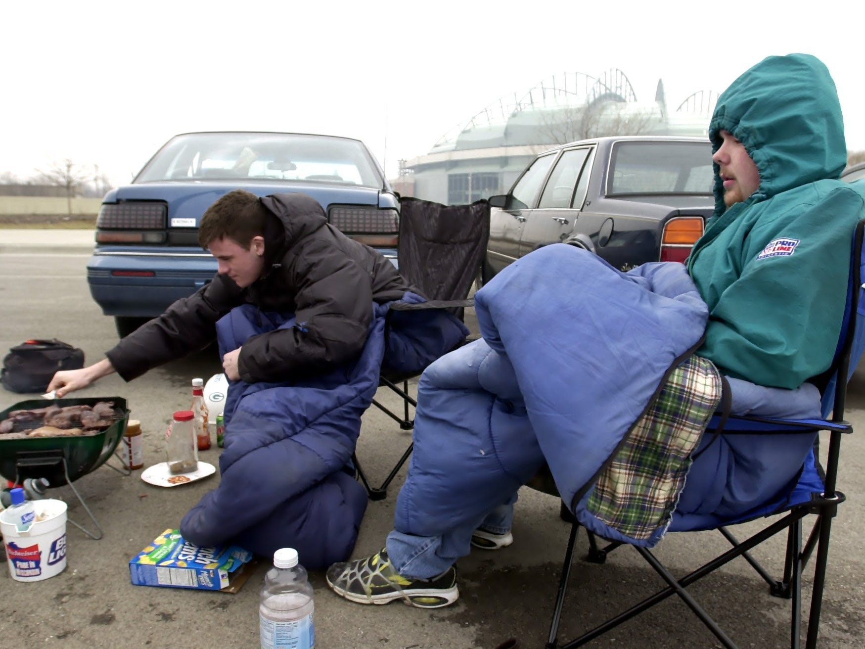 """Miller Park has a retractable roof, but not so the parking lot for tailgaters on April 6, 2001, opening day for the 2001 season. Christopher VerVelde (from left) and Williams Capello tailgate in the parking lot but didn't have tickets for the sold-out game. """"We basically came to grill and have a good time,"""" said Capello.   Inside Miller Park, the Milwaukee Brewers beat the Cincinnati Reds, 5-4."""