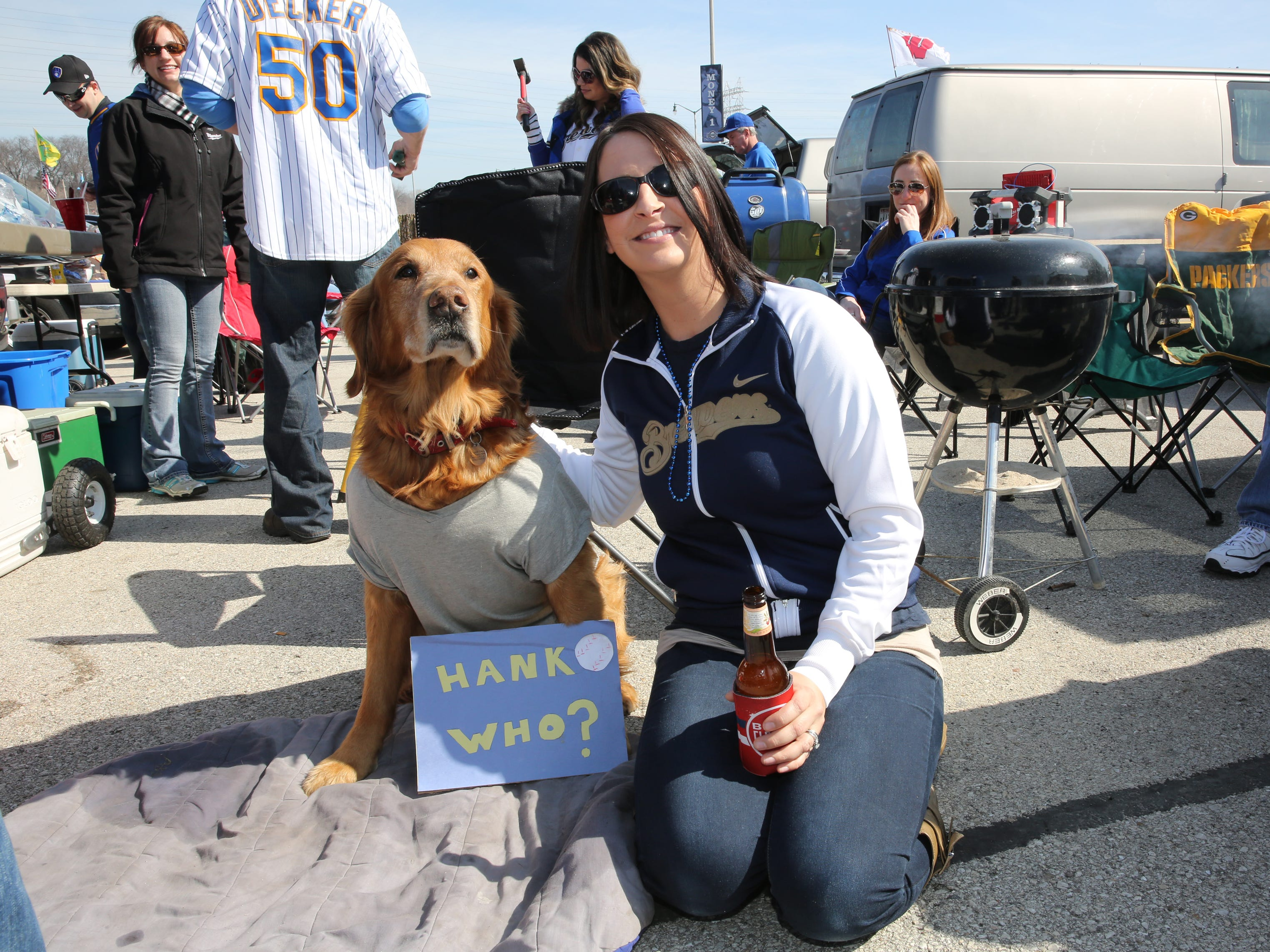 Katie Pfister of Menomonee Falls poses with Chance, a golden retriever owned by Josh Larson, of Milwaukee as they tailgate before the Milwaukee Brewers faced the Colorado Rockies for the home opener at Miller Park on April 6, 2015. The Rockies won, 10-0.