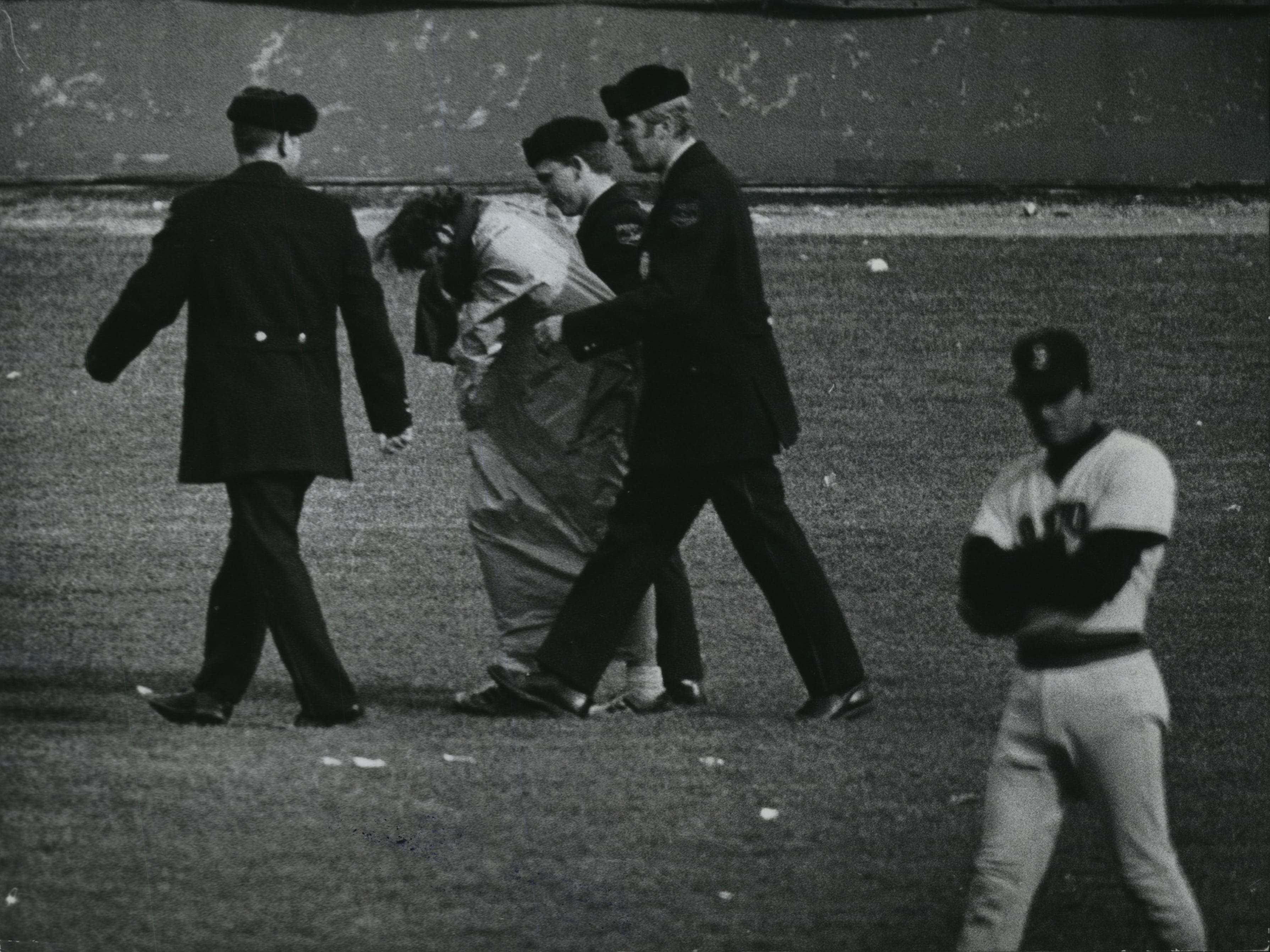 Three Milwaukee police officers escort a young man from the outfield after the man tried to streak across the field bottomless (as in, no pants), despite the day's freezing temperatures, at the Brewers' 1974 home opener at County Stadium on April 5, 1974. This photo was published in the April 6, 1974, Milwaukee Journal.