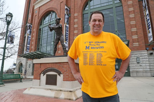 Jay Saeger stands beside the Henry Aaron statue at Miller Park. Saeger cut school in the seventh grade to attend the Brewers first home opener and he's been to every single one since then.  This will be his 50th and he's had T-shirts made up for him and his friends to wear.