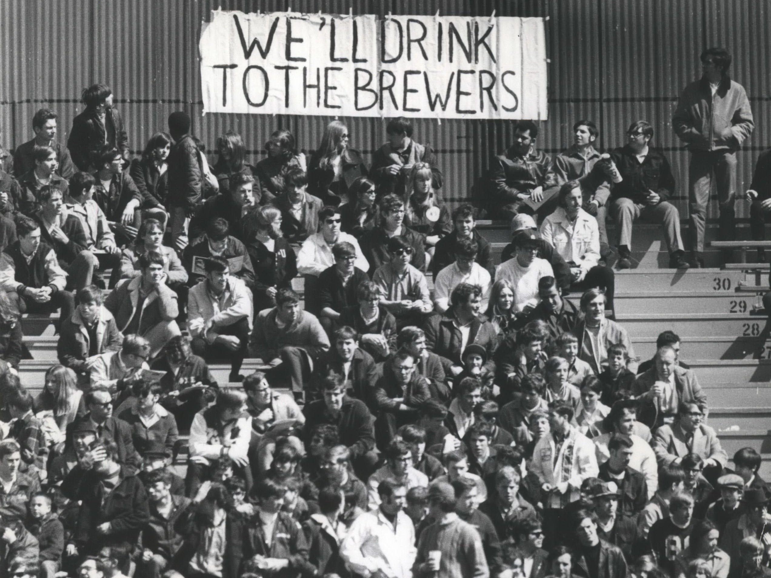Fans in the bleachers drink a toast to the Milwaukee Brewers on April 7, 1970, the Brewers' first-ever opening day at County Stadium. The Brewers lost to the California Angels, 12-0.