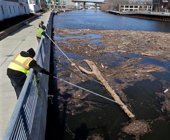 Milwaukee Department of Public Works workers use long poles to try to guide logs downstream into moving waters of the Milwaukee River at a logjam of trees, branches and debris at the Pleasant Street Bridge on Tuesday.