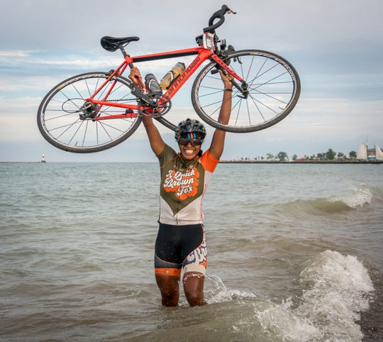 Ayesha McGowan, the first black female professional racing cyclist, celebrates at Simmons Island Beach in Kenosha after riding from the Mississippi River to the shore of Lake Michigan in the 2016 Ride Across Wisconsin.