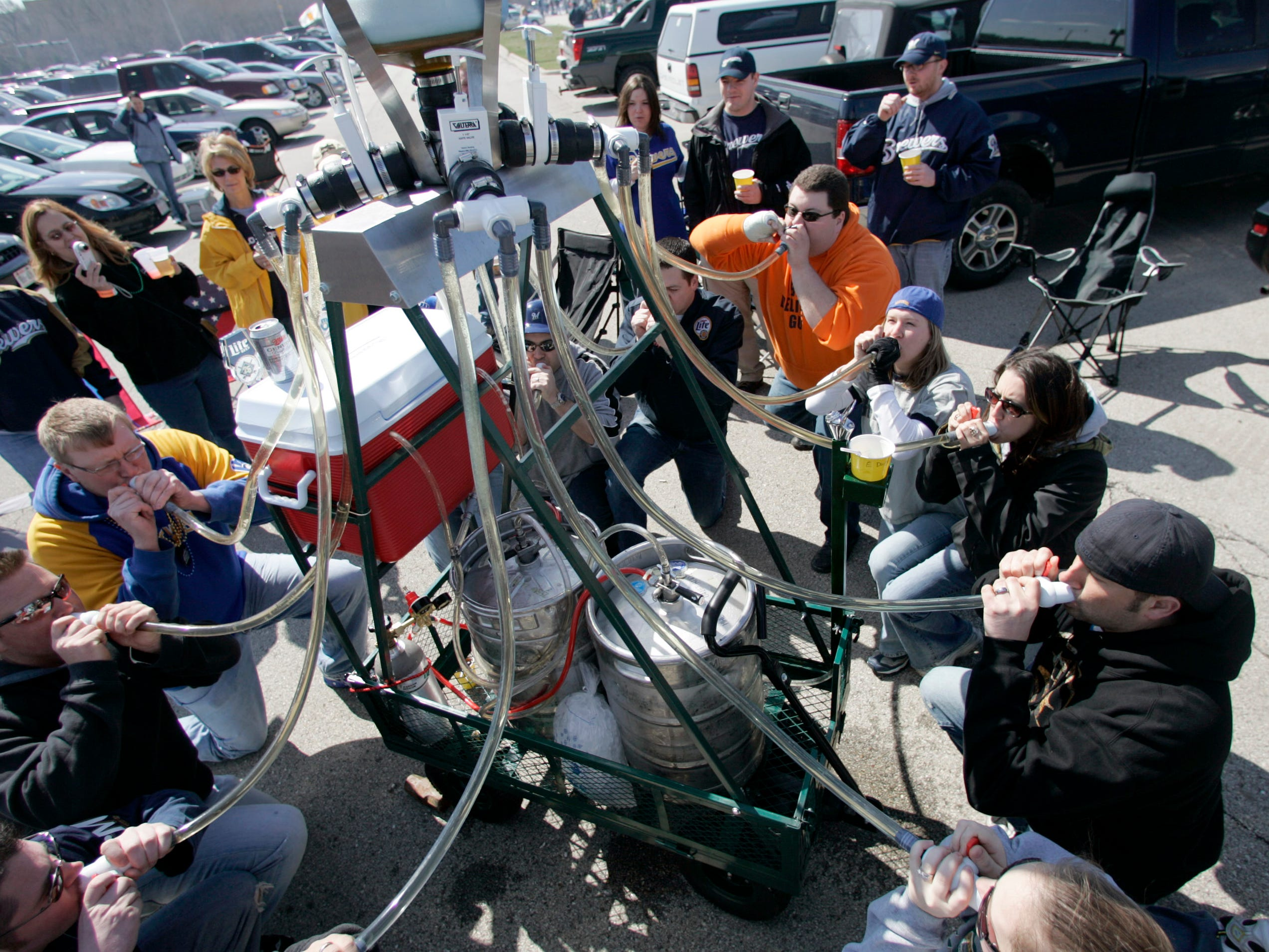 Twelve people try out a 12-person beer bong created by Jeff Barton of Milwaukee (in orange), before opening day at Miller Park on April 2, 2007. Barton designed the contraption, which weighs 600 pounds fully loaded and serves two beers per person when doing a group drink. It also has a fully functioning beer bubbler. Oh, yeah: In the game inside Miller Park, the Milwaukee Brewers defeated the Los Angeles Dodgers, 7-1.