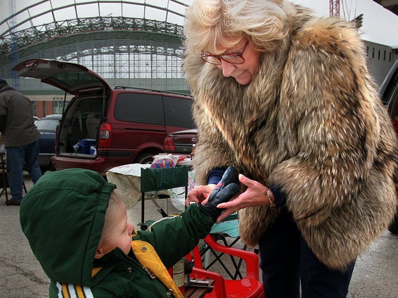 Dressed appropriately for the final opening day at County Stadium, Meredith Bodovinac put mittens on her grandson, Brandon Michalowski, during a tailgate party before the game on April 10, 2000. Miller Park, still under construction, is in the background. In the game, the Milwaukee Brewers beat the Florida Marlins, 4-3.