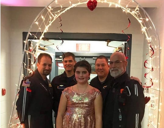 After her father died suddenly last year, Kylie Logan, 10, was left without a date for a father-daughter dance. Attending in his absence were members of flight paramdeic Patrick Logan's Atlantic Mobile Health flight team: from left, Art Samaras, Morgan Troisi, Paul Horsey, and Jim McGrath.