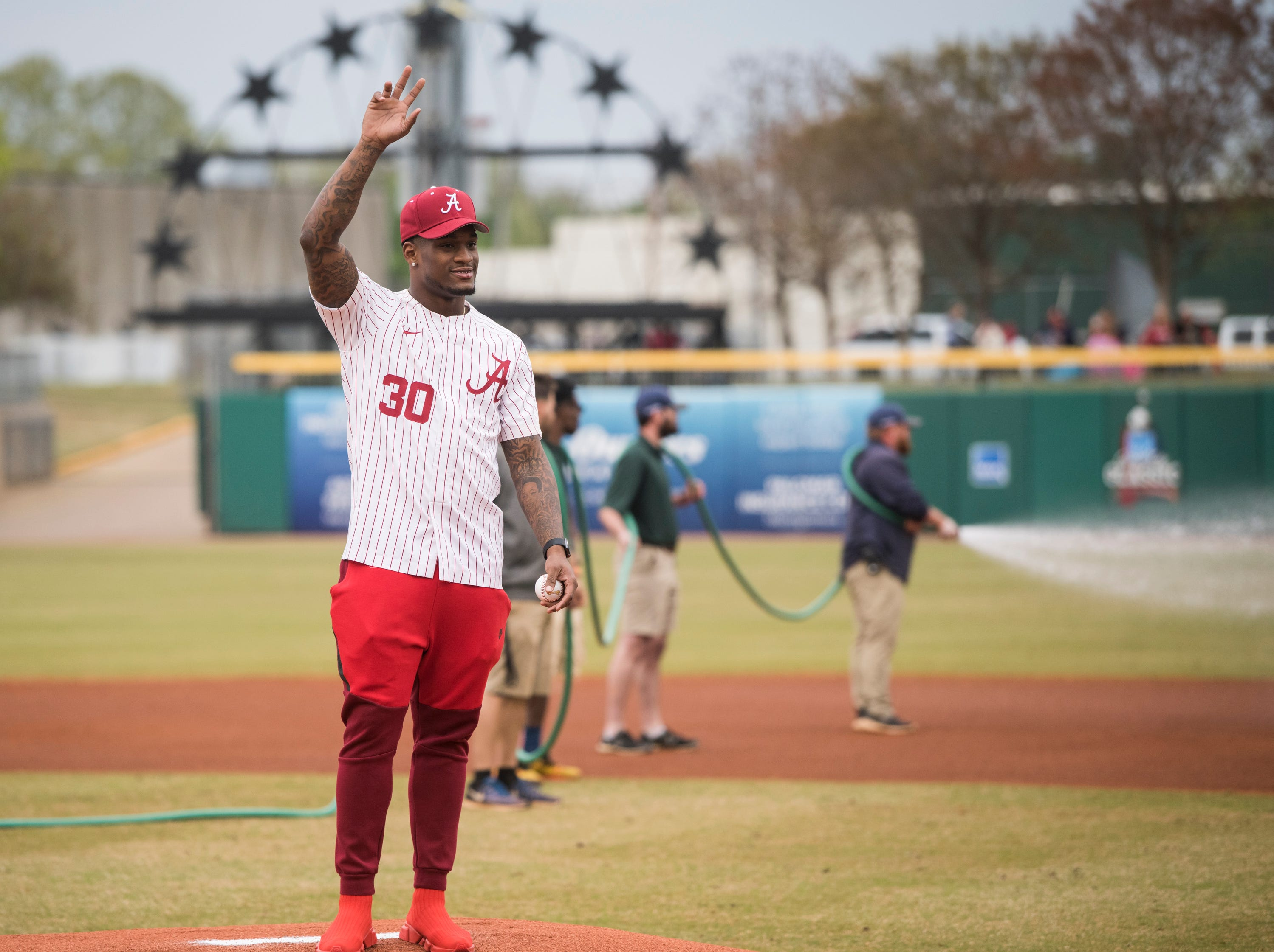 former Alabama linebacker Mack Wilson acknowledges the crowd before throwing out the first pitch during the Auburn-Alabama Capital City Classic at Riverfront Park in Montgomery, Ala., on Tuesday, March 26, 2019.