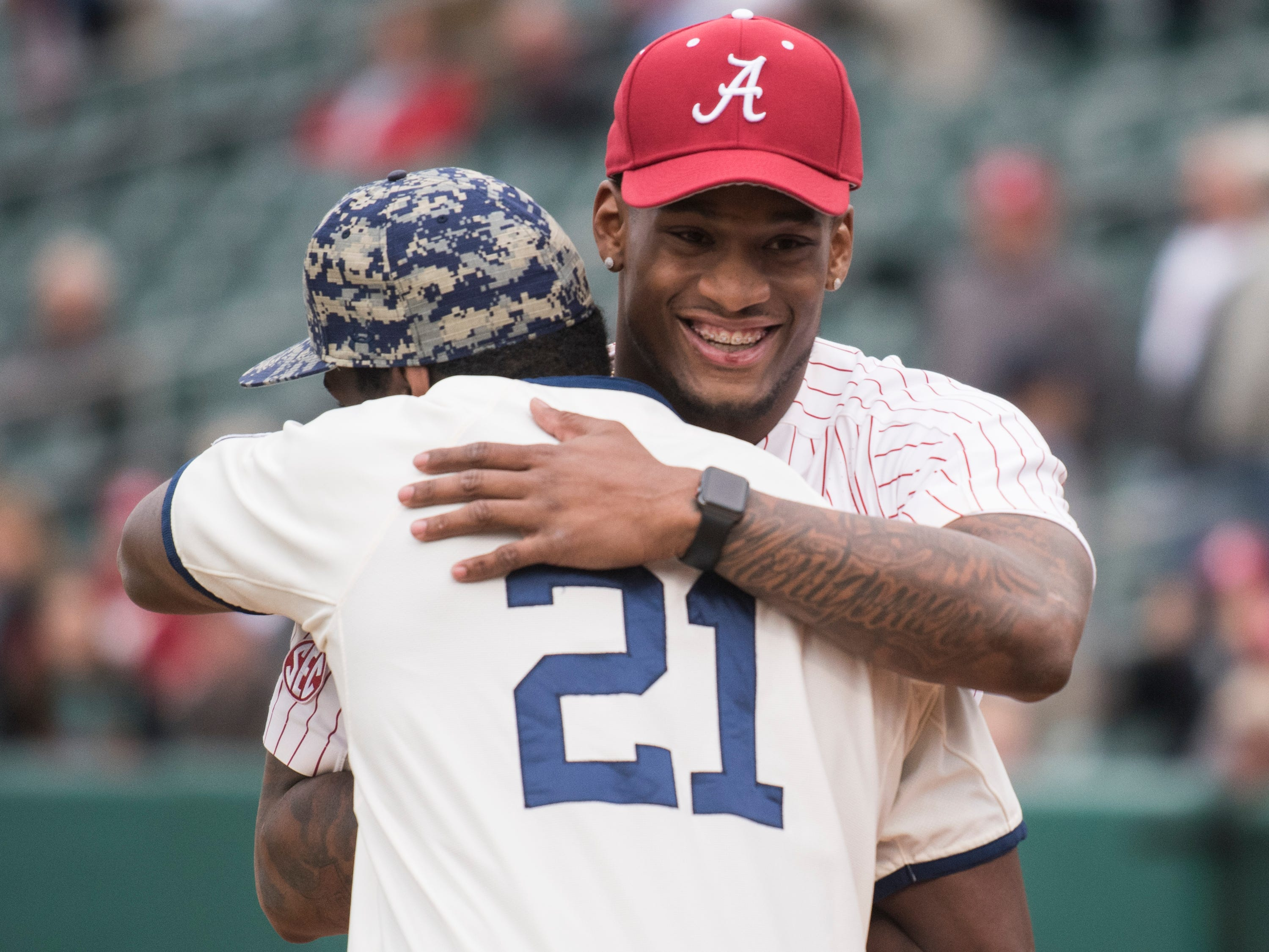 Former Auburn running back Kerryon Johnson and former Alabama linebacker Mack Wilson hug as they both throw out the first pitch during the Auburn-Alabama Capital City Classic at Riverwalk Stadium in Montgomery, Ala., on Tuesday, March 26, 2019.