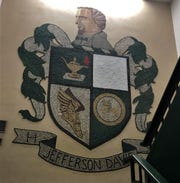 The Jefferson Davis High School crest displayed at the landing of one of its main stairwells. The top-right corner of the crest formerly showed the Confederate flag until painted over by the school's current administration.