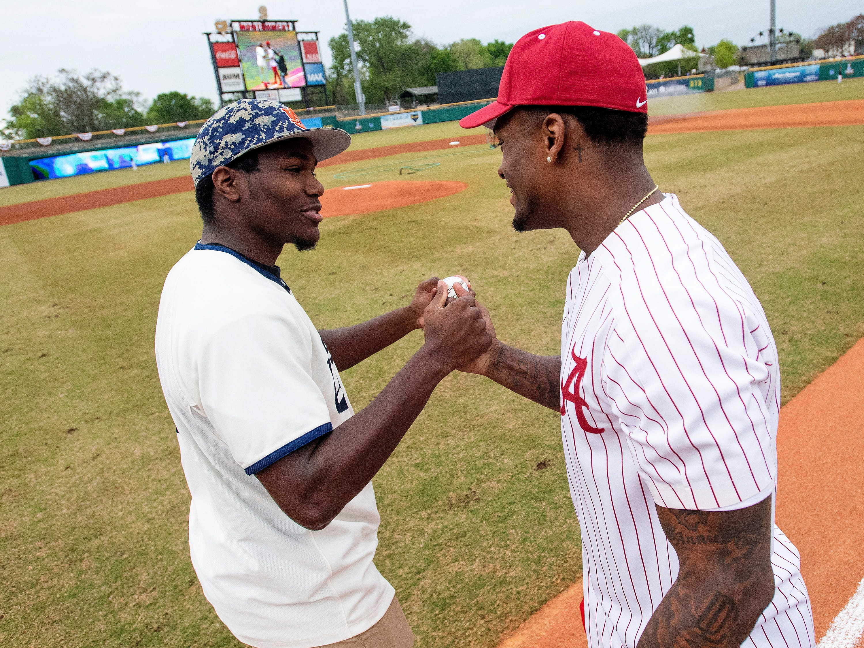 Former Auburn running back and current Detroit Lions running back Kerryon Johnson and former Alabama linebacker, who is going into next months NFL draft, Mack Wilson greet as they throw out ceremonial first pitches at the MAX Capital City Classic at Riverwalk Stadium in Montgomery, Ala., on Tuesday March 26, 2019.
