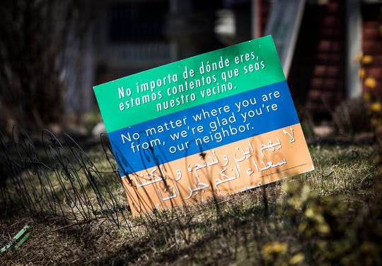 A yard sign in the Old West End Neighborhood welcomes new neighbors in English, Spanish and Arabic.