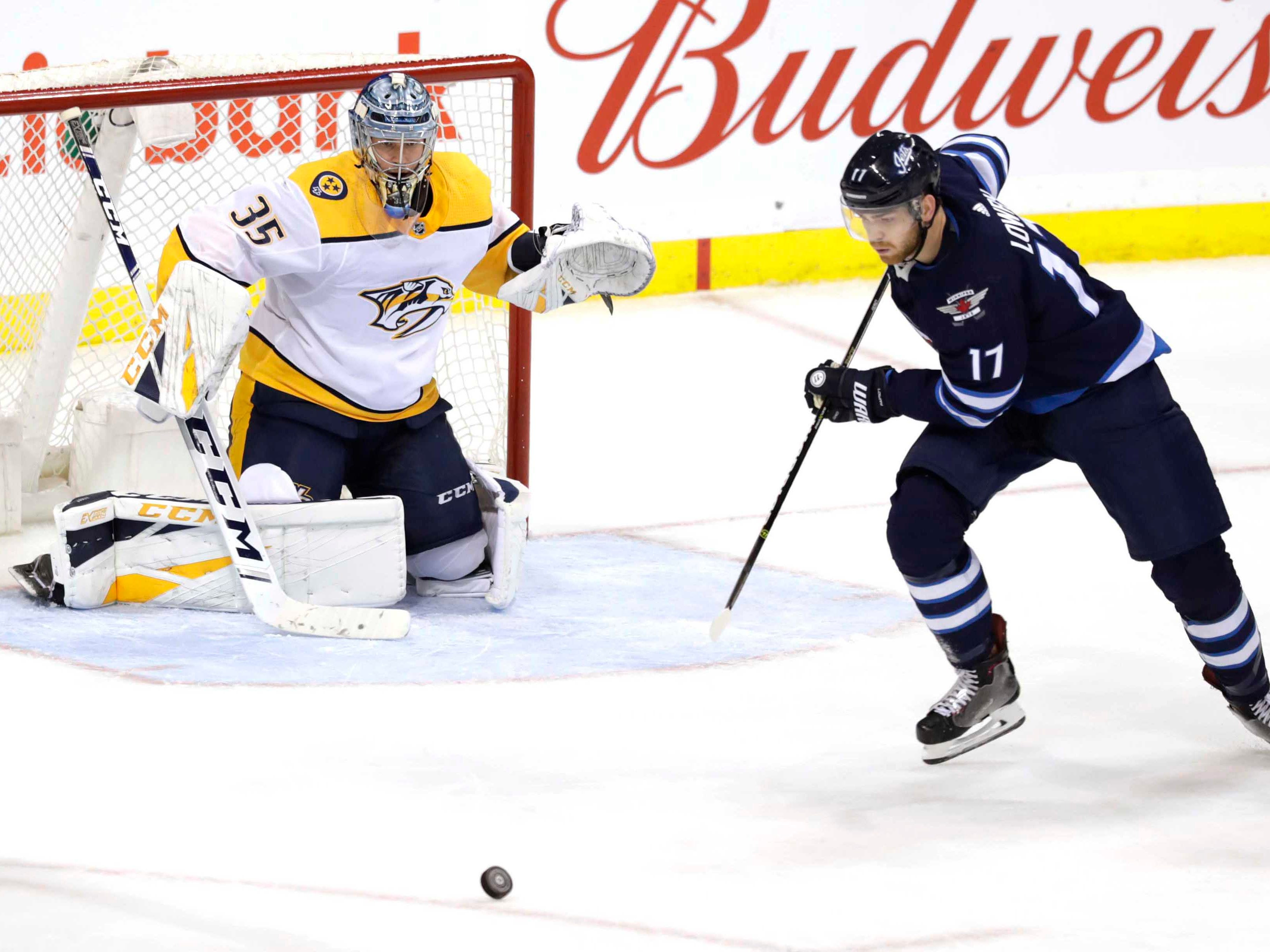 Winnipeg Jets center Adam Lowry (17) chase down the puck in front of Nashville Predators goaltender Pekka Rinne (35) in the third period at Bell MTS Place.