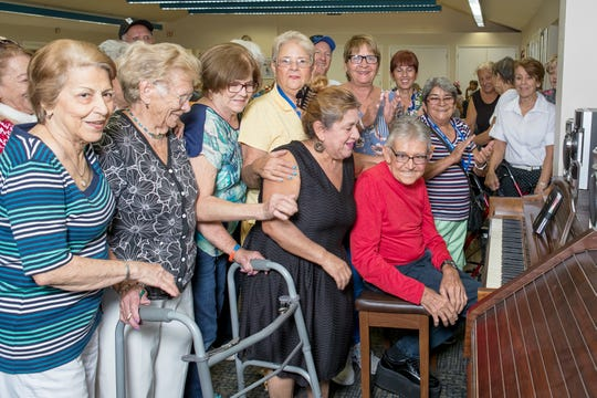 Members of the Golden Gate Senior Center gather around for the piano to sing some favorite songs.