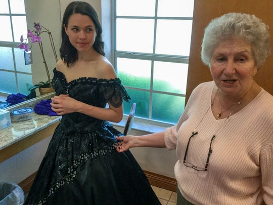 Maria Valdes, who stars as Violetta, gets some last minute adjustments from costume designer Ena Gleeson on her opening scene party gown.