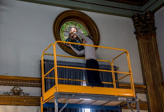 A worker from Conrad Schmitt Studios Inc., in New Berlin, Wisconsin, installs a restored Tiffany stained-glass window depicting Ben Franklin in the historic west courtroom of the Licking County Courthouse. Five restored windows were reinstalled in the courtroom.