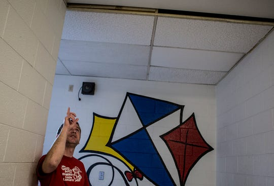 Hebron kindergarten teacher Brian Brown points out a place where ceiling tiles at Hebron Elementary have been replaced multiple times due to water leaks. He still must put buckets and trash cans out to catch the water there when it rains at the 105-year-old school.
