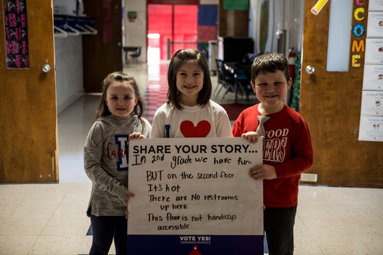 Hebron Elementary second graders Ella Misner, Reagan Biddle and Noah Marietta-Brown hold a sign in the second grade hallway listing some of the many problems with their corner of the school.