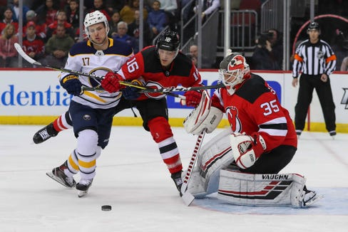 Mar 25, 2019; Newark, NJ, USA; Buffalo Sabres center Vladimir Sobotka (17) and New Jersey Devils defenseman Steven Santini (16) battle for the puck after a save by New Jersey Devils goaltender Cory Schneider (35) during the first period at Prudential Center.