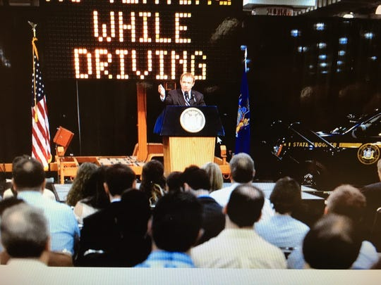 John Corlett, director of public affairs and government relations at AAA Northeast, speaks at an event with New York governor Andrew Cuomo and members of law enforcement.