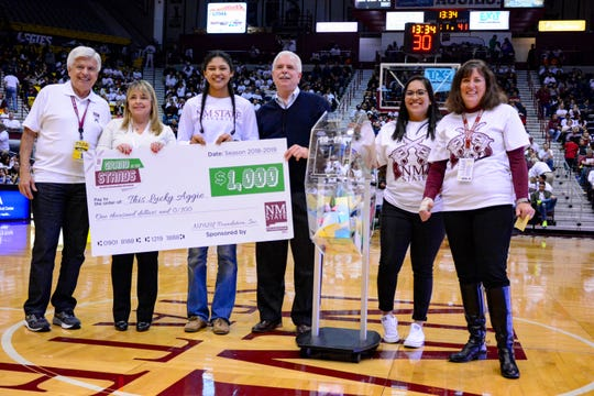 """Alyssa Magana, third from left, is one of seven winners of """"A Grand in the Stands!,"""" a $1,000 scholarship giveaway sponsored by the NMSU Foundation. The giveaway asked students to enter the drawing using their Aggie ID at the games. A giant, spinning wheel contained every registered student's name, and at the start of halftime, one name was picked. Magana was picked during the NM State vs. GCU game on January 10."""