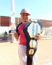 Las Cruces Dawgs youth baseball team member Santino Lozoya on Sunday, March 24, 2019 holds a trophy and prize belt awarded for the team's win in the USSSA Bataan Death March Memorial Super NIT.