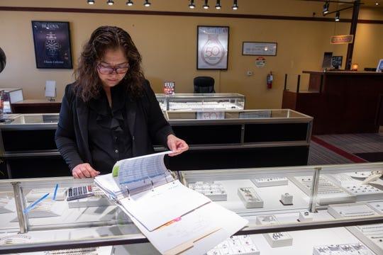 Holandesa Lopez inventories jewelry at her work. Andrew Nixon / Capital Public Radio