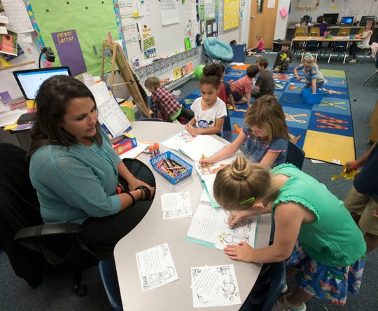 Kindergarten teacher Amy Oswalt works with a small group of students at Oriole Beach Elementary School in Gulf Breeze on Tuesday, March 26, 2019. Oriole Beach Elementary is one of several schools in the Santa Rosa County school district that will be rezoned next year.