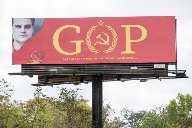 """Matt Gaetz's mug shot is featured on a billboard that says """"GOP"""" with the Communist hammer and sickle for the """"O"""" displayed near along North W Street north of West Fairfield Drive in Pensacola on Tuesday, March 26, 2019.  The billboard was paid for and approved by the Mad Dog PAC."""