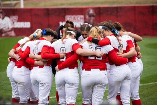 Hayley Norton (No. 9) huddles with her St. Francis University teammates during a softball game.