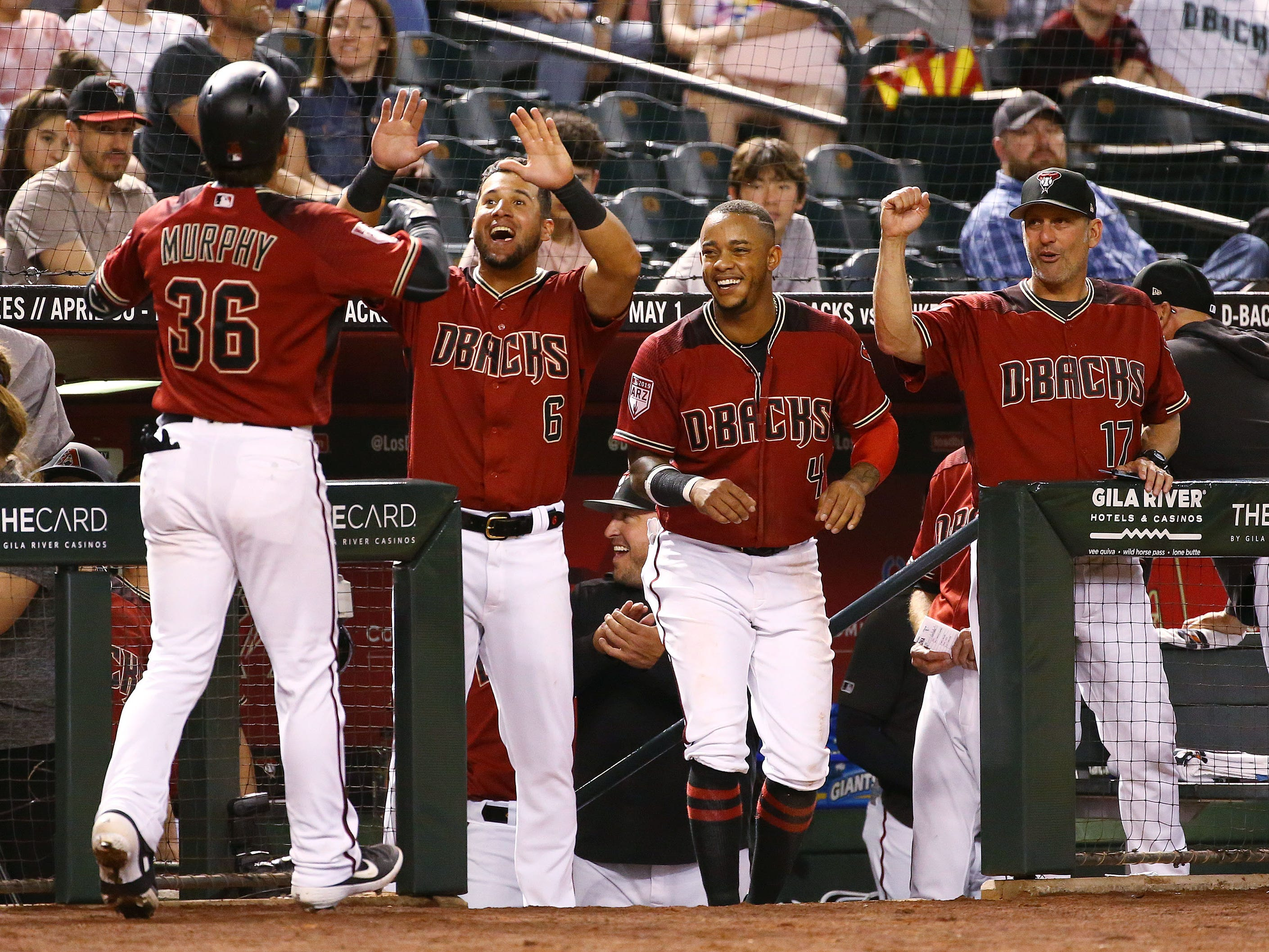 Arizona Diamondbacks John Ryan Murphy (36) celebrates with teammates David Peralta (6), Ketel Marte (4) and manager Torey Lovullo (right) after hitting as solo home run against the Chicago White Sox in the third inning during a spring training game on Mar. 25, 2019 at Chase Field in Phoenix, Ariz.