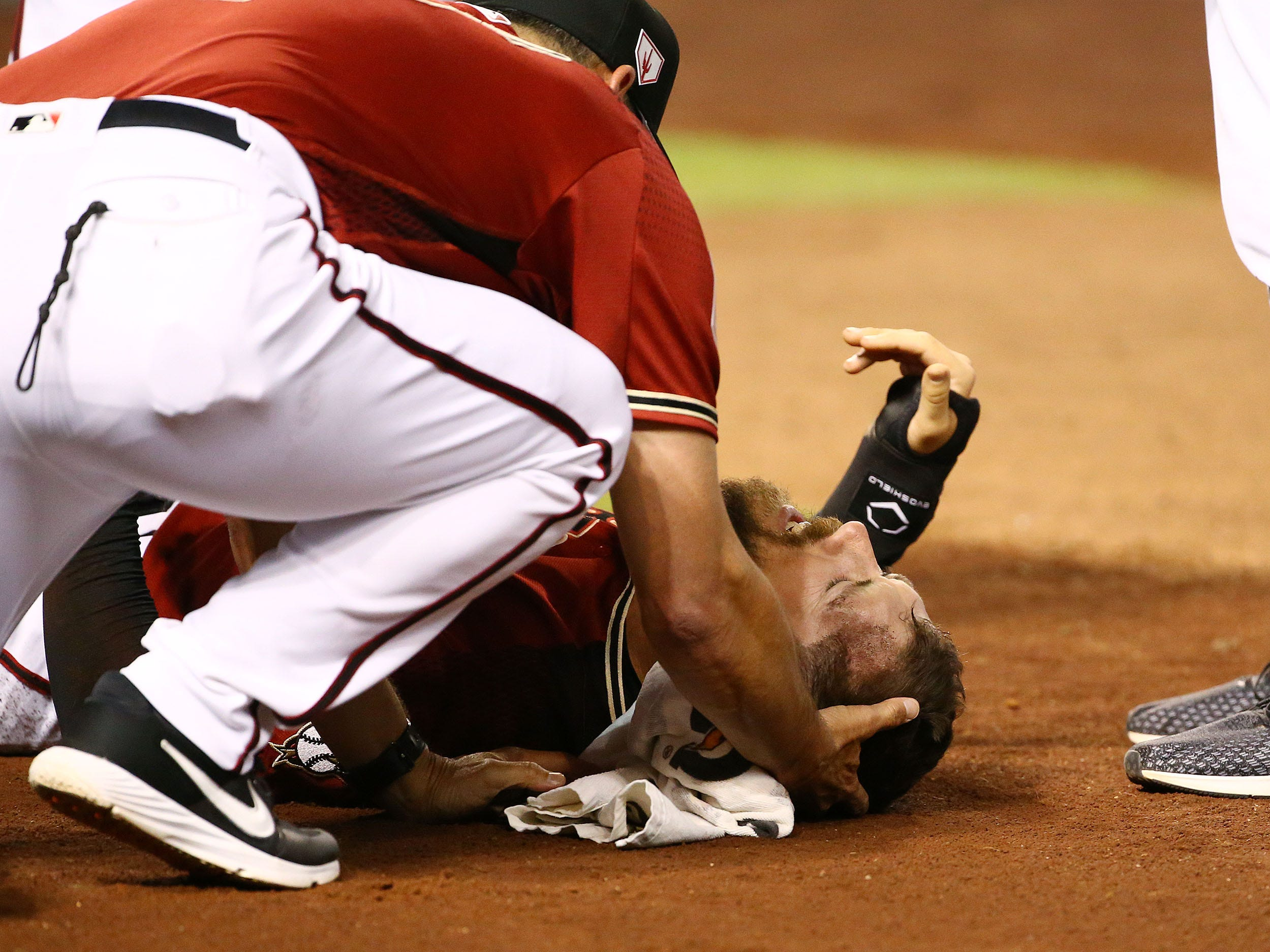 Arizona Diamondbacks manager Torey Lovullo comforts Steven Souza Jr. after suffering an injury to his leg against the Chicago White Sox in the fourth inning during a spring training game on Mar. 25, 2019 at Chase Field in Phoenix, Ariz.