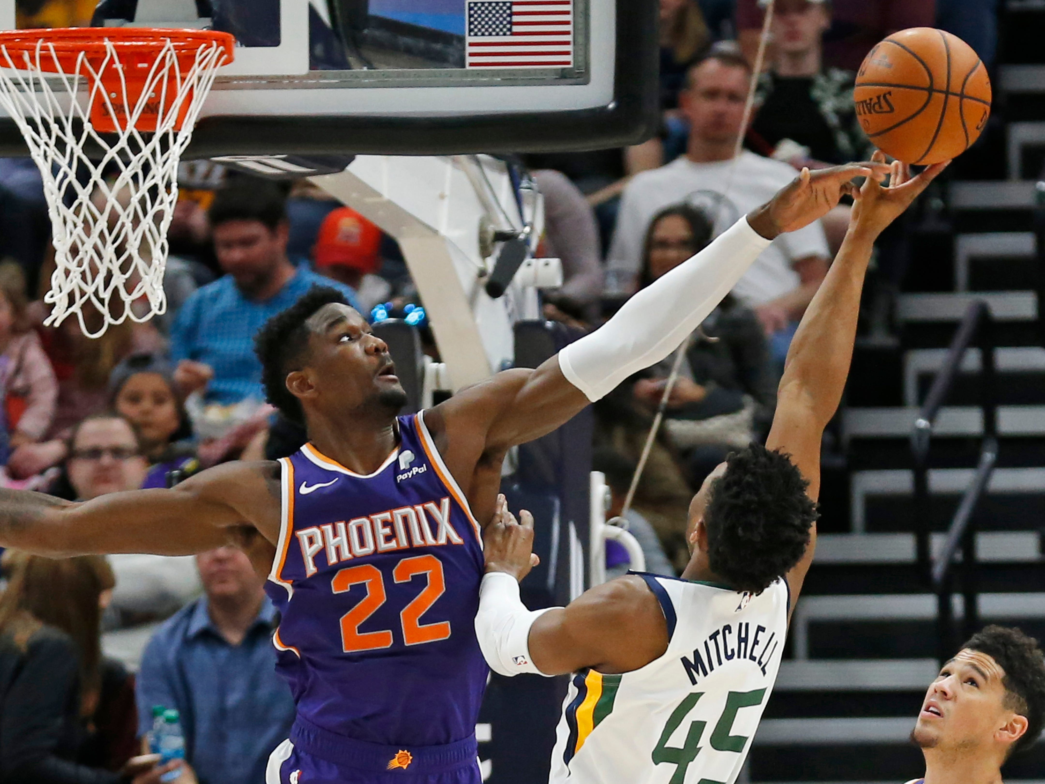 Phoenix Suns center Deandre Ayton (22) defends against Utah Jazz guard Donovan Mitchell (45) during the first half of an NBA basketball game Monday, March 25, 2019, in Salt Lake City.