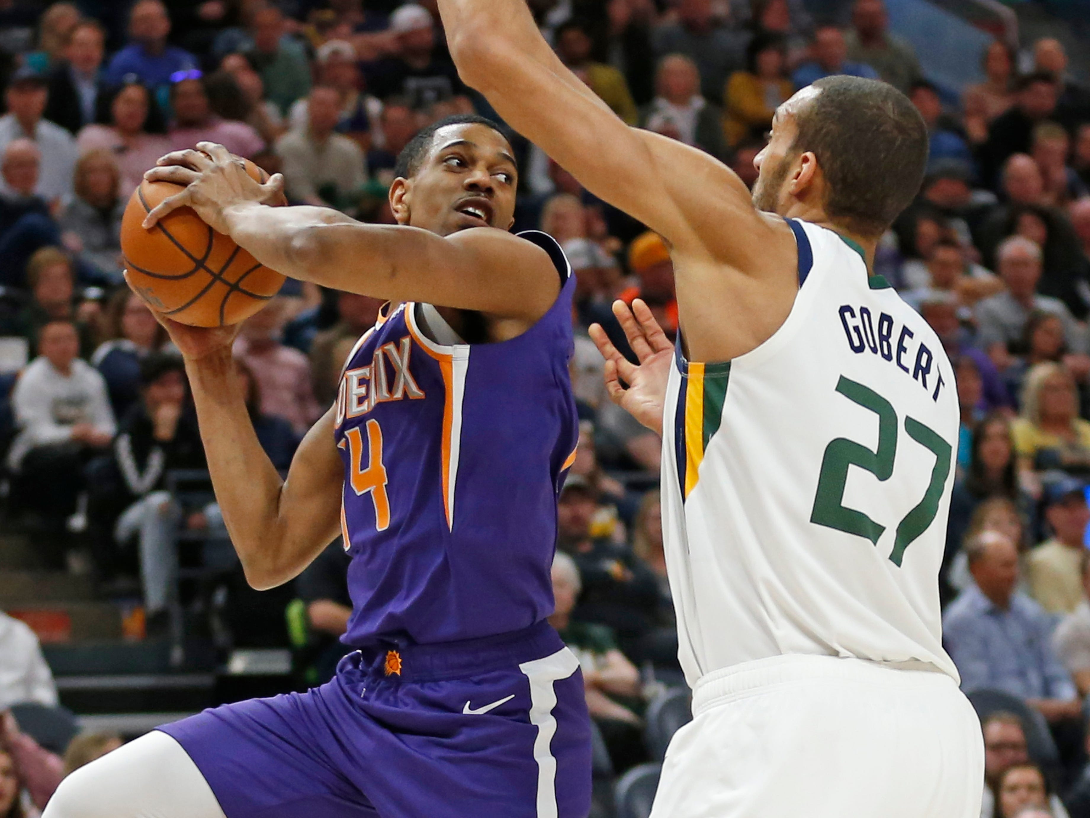Phoenix Suns guard De'Anthony Melton, left, passes the ball as Utah Jazz center Rudy Gobert (27) defends during the first half of an NBA basketball game Monday, March 25, 2019, in Salt Lake City.