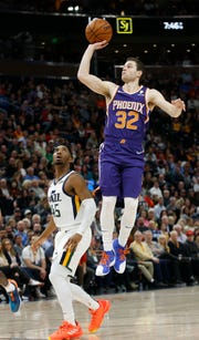 Phoenix Suns guard Jimmer Fredette (32) shoots as Utah Jazz guard Donovan Mitchell (45) looks on during the first half of an NBA basketball game Monday, March 25, 2019, in Salt Lake City.