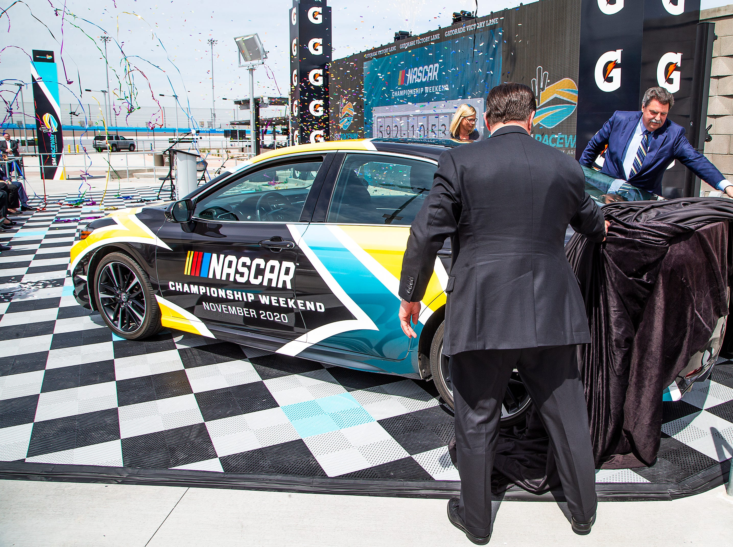 Gov. Doug Ducey (left) and NASCAR Vice Chairman Mike Helton help unveil a NASCAR vehicle with the logo of the NASCAR Championship Weekend on March 26, 2019, after it was the announced that NASCAR will be moving the championship to ISM Raceway in Avondale.