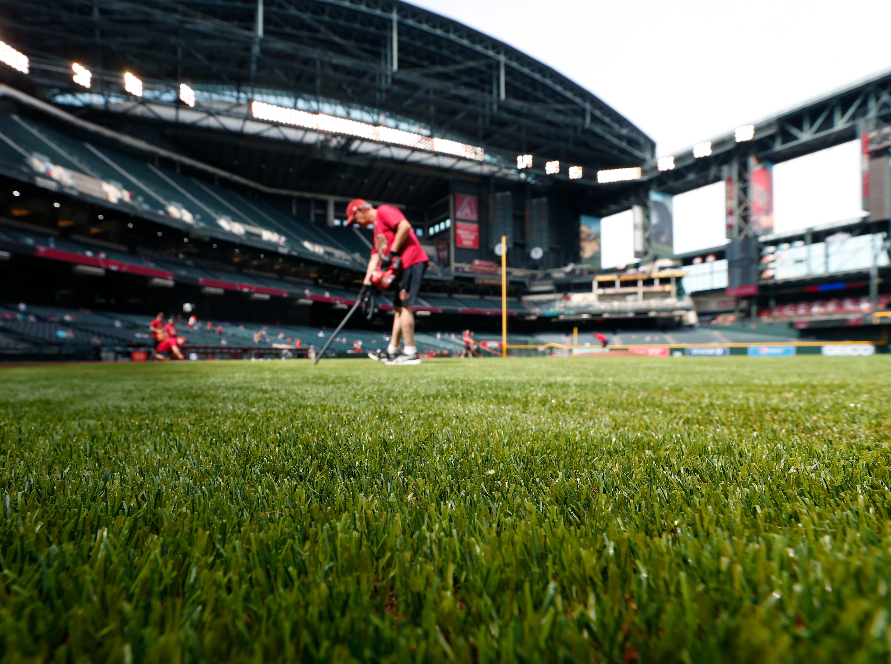 Chase Field grounds crew worker Mike Smothers uses a vacuum to clean up the new artificial turf before spring training action between the Arizona Diamondbacks and the Milwaukee Brewers March 26, 2019.