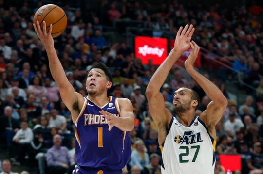 Phoenix Suns guard Devin Booker (1) lays up the ball as Utah Jazz center Rudy Gobert (27) defends during the first half of an NBA basketball game Monday, March 25, 2019, in Salt Lake City.