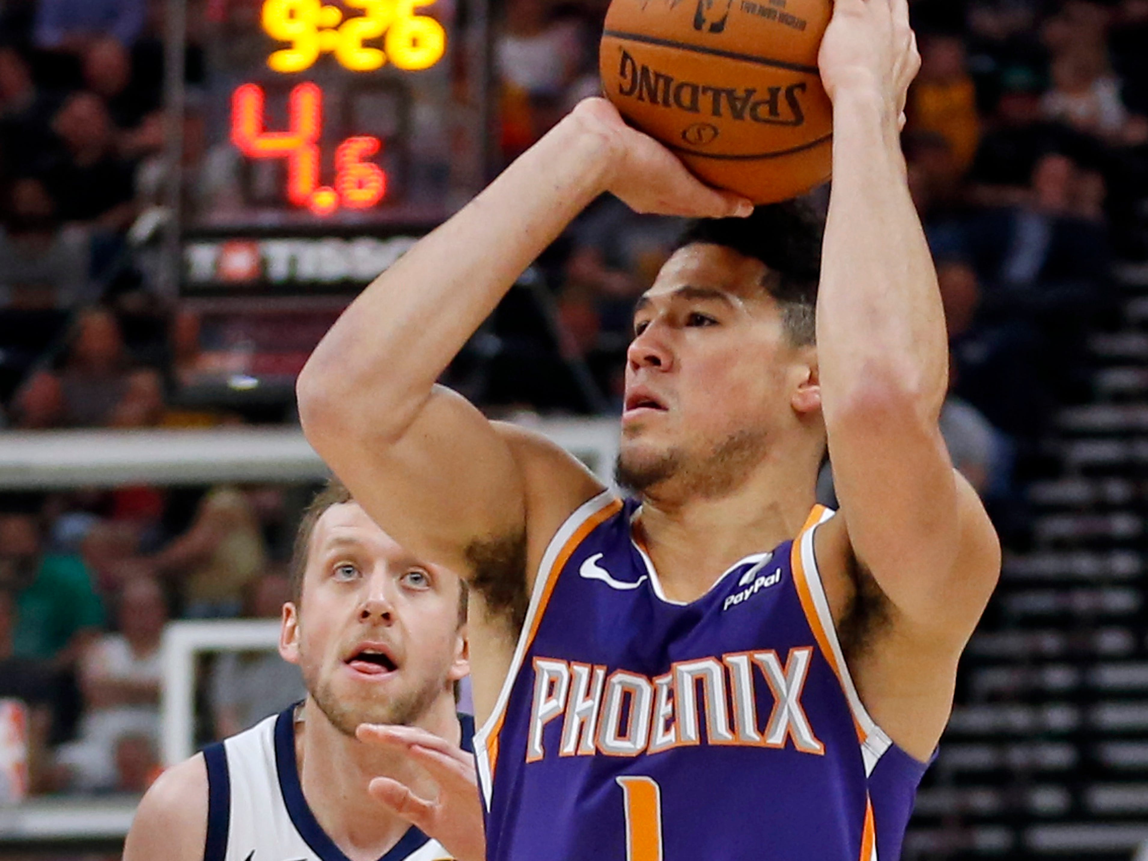 Phoenix Suns guard Devin Booker (1) prepares to shoot as Utah Jazz forward Joe Ingles (2) defends during the first half of an NBA basketball game Monday, March 25, 2019, in Salt Lake City.