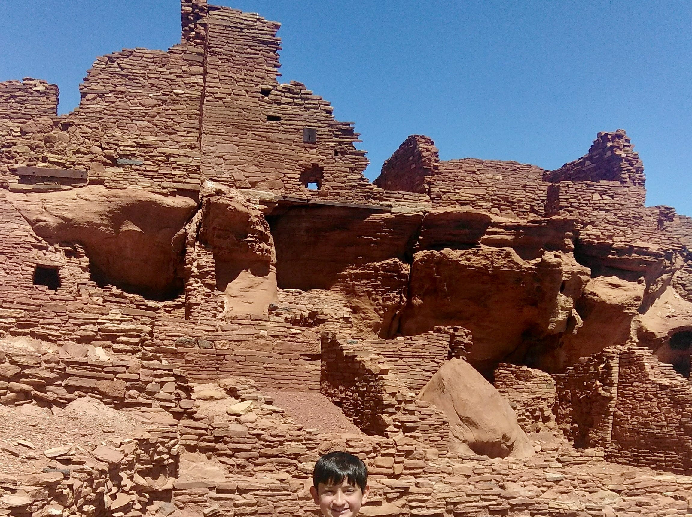 Bryan Wilson, 12, at Wupatki National Monument wearing his vest covered with Junior Ranger badges. Kids can earn badges by completing educational activities at national parks and sites.