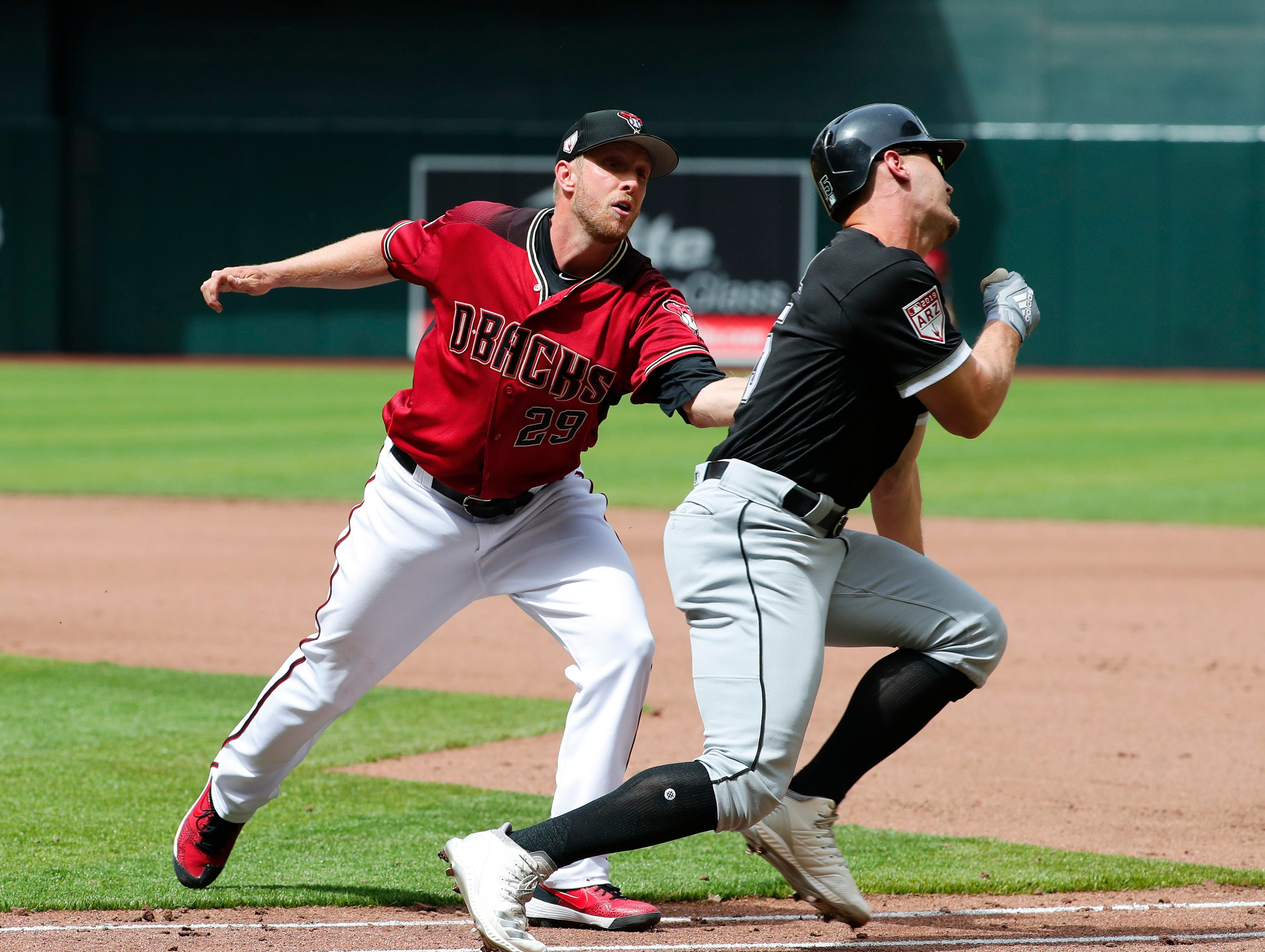 Arizona Diamondbacks starting pitcher Merrill Kelly (29) tags out Chicago White Sox base runner Adam Engel (15) during spring training action at Chase Field March 26, 2019.