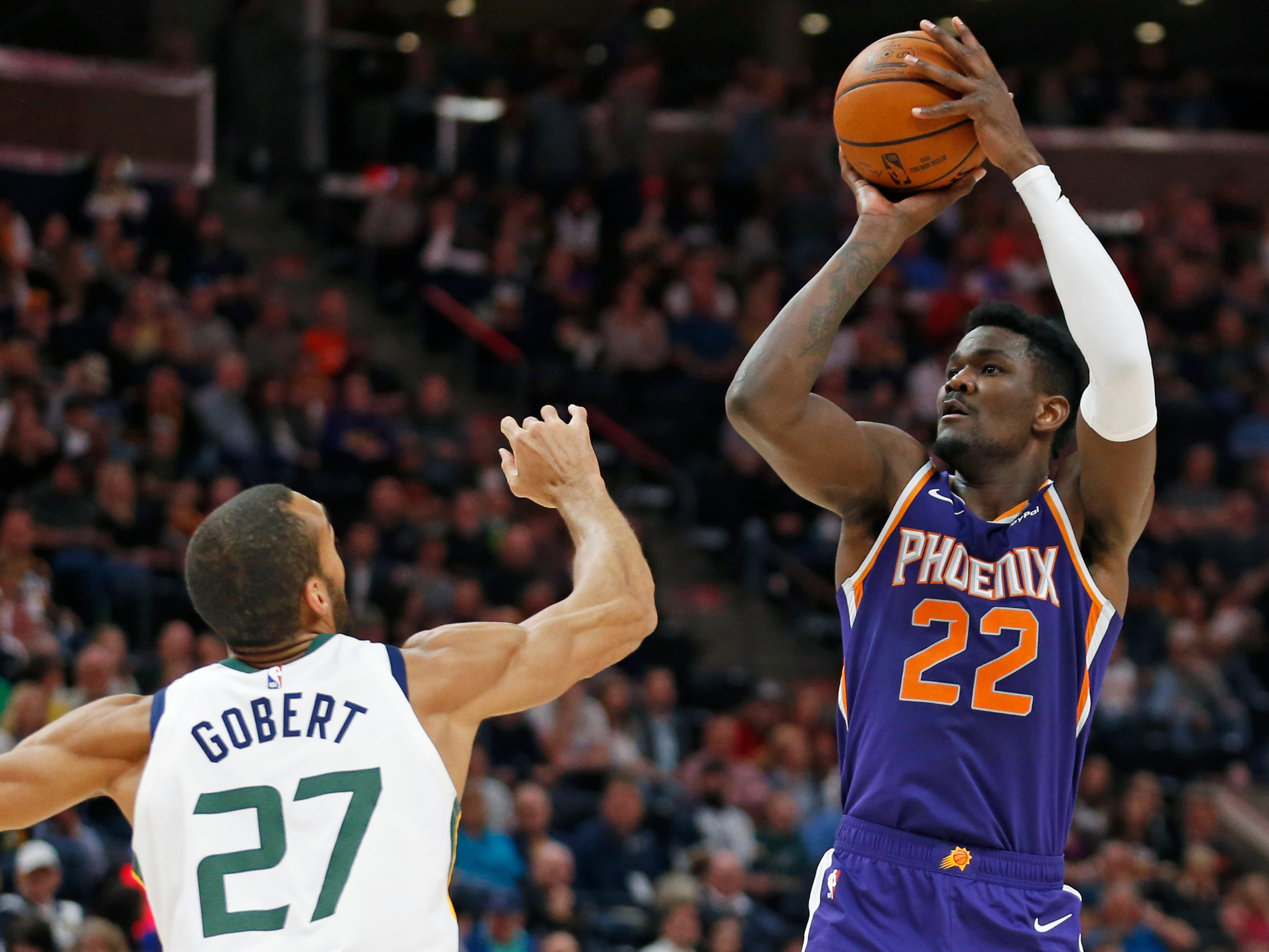 Phoenix Suns center Deandre Ayton (22) shoots as Utah Jazz center Rudy Gobert (27) defends during the first half of an NBA basketball game Monday, March 25, 2019, in Salt Lake City.