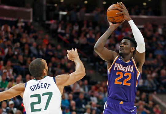 Deandre Ayton shoots over Jazz center Rudy Gobert during a game on March 25.
