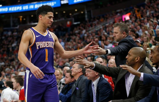 The Phoenix Suns bench reaches for guard Devin Booker (1) as he leaves during the second half of the team's NBA basketball game against the Utah Jazz on Monday, March 25, 2019, in Salt Lake City.