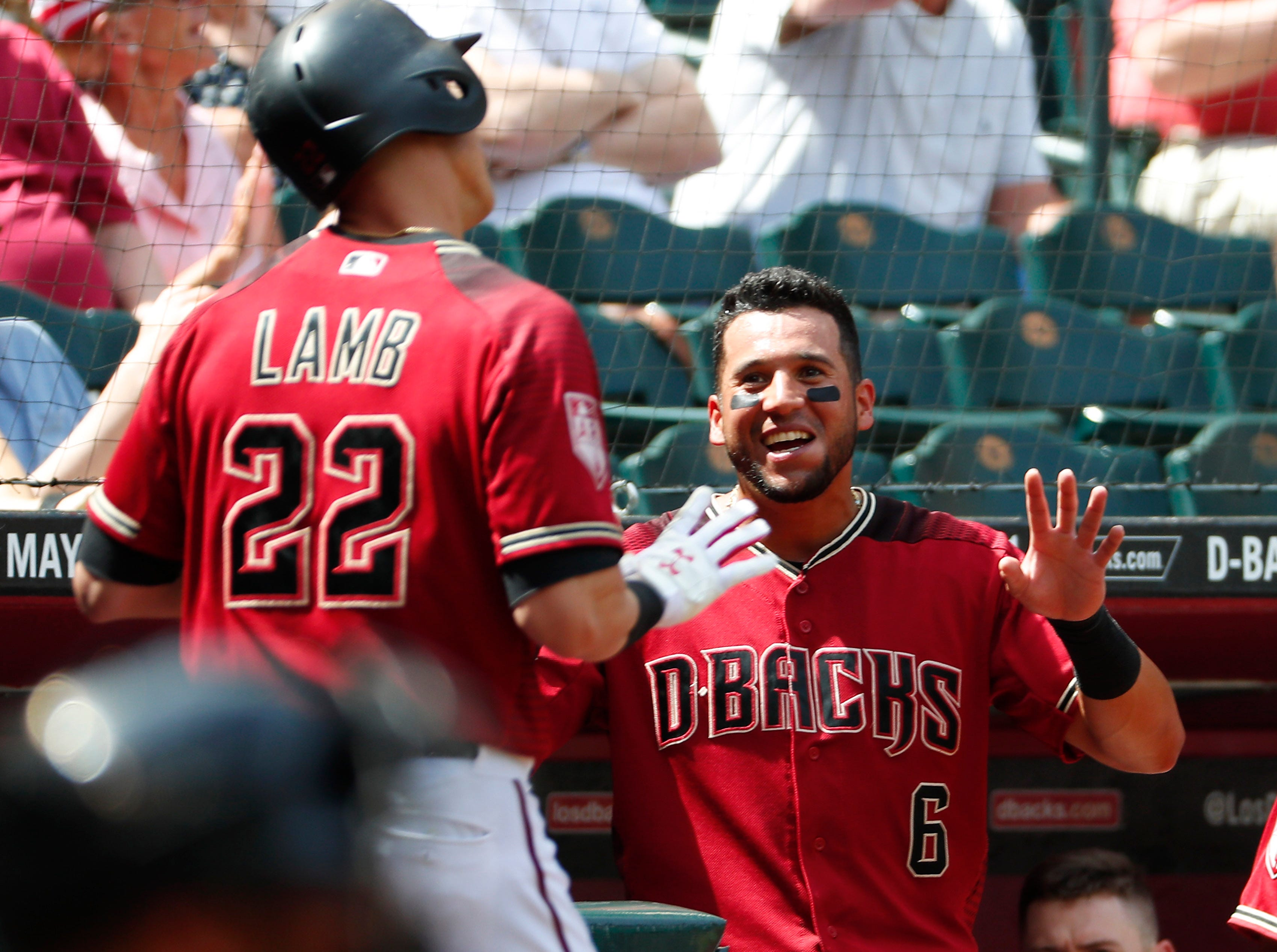 Arizona Diamondbacks first baseman Jake Lamb (22) is congratulated by left fielder David Peralta (6) after hitting a solo home run against the Chicago White Sox during spring training action at Chase Field March 26, 2019.
